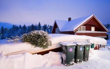 Et hus med avfallsbeholdere utenfor, om vinteren.